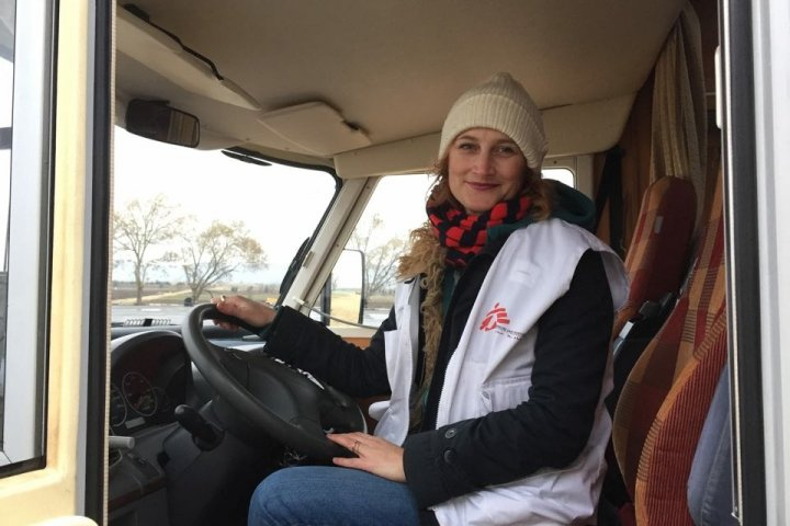 sjuksköterskan Anna Sjlblom sitter vid ratten i en lastbil i Grekland. Hon har en vit väst mer Läkare utan gränser-loggan på
