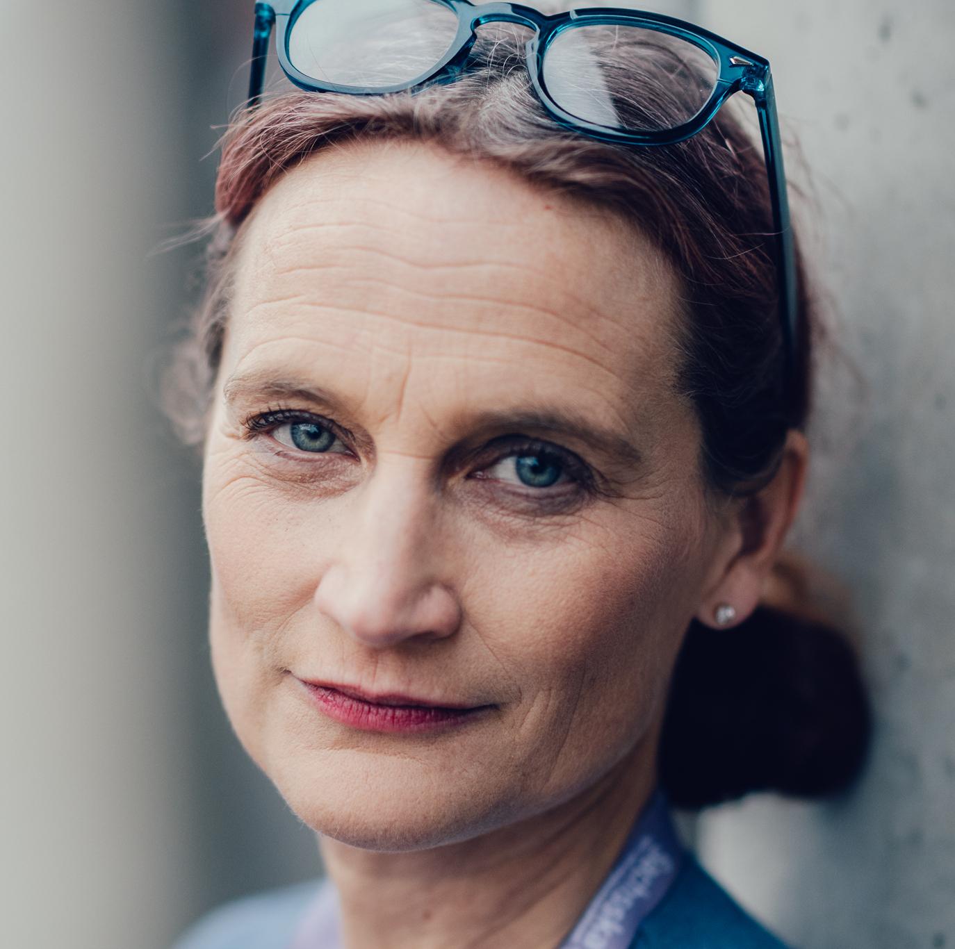 Porträtt Anna Sjöblom med glasögon uppe på huvudet