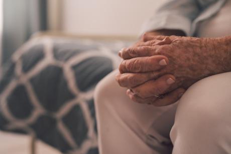 Äldre person med händerna knäppta.