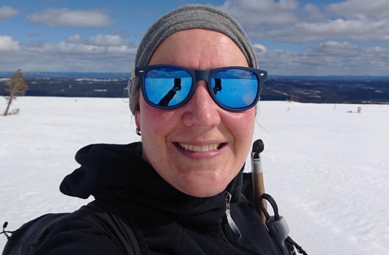 Porträttbild på sjuksköterskan Britta Gunnarsson med solglasögon i fjällen