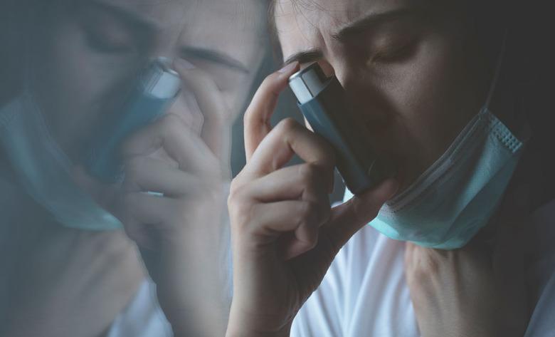 Kvinna med munskydd och astmainhalator.