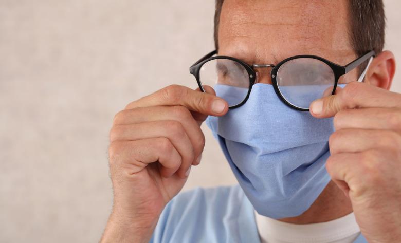 Man med immiga glasögon och munskydd.