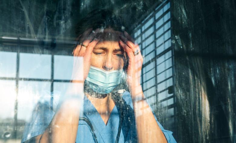 Kvinna i sjukhuskläder med huvudvärk sedd genom ett fönster.