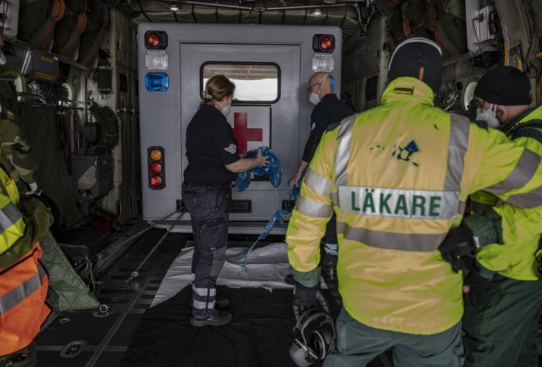 personal från Liv iutanför ambulansen inuti ett Herkulesplan