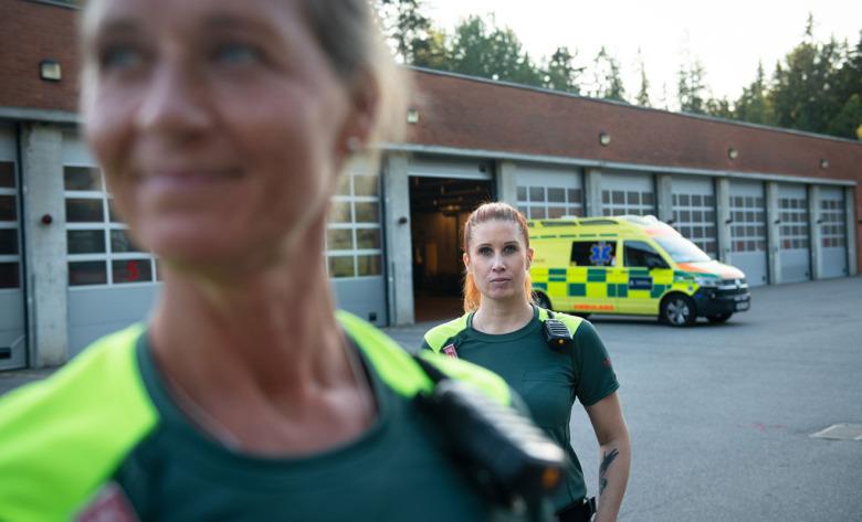 Åsa Jonsson, ambulanssjukvårdare, och Linda Orrvik, ambulanssjuksköterska, framför ambulansen. Foto: Anders G Warne